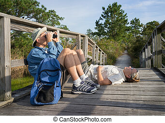 Seniors birdwatching and relaxing on old wooden footbridge