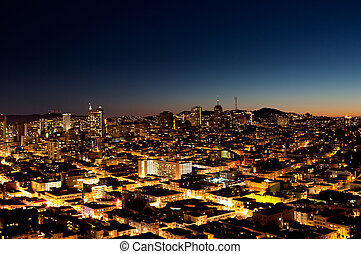 City at Night - A view of a city at night with a sunset on...
