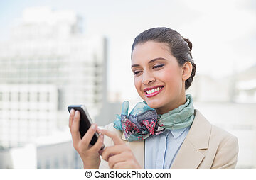 Amused smart brown haired businesswoman using a mobile phone