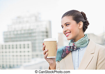 Happy smart brown haired businesswoman holding a cup of...