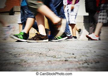Walking on urban street - People legs walking on paved urban...