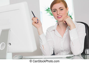 Stern businesswoman working at her desk holding pen in her...
