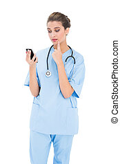 Troubled brown haired nurse in blue scrubs using a mobile...