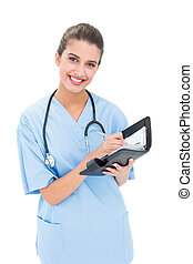 Content brown haired nurse in blue scrubs filling an agenda...