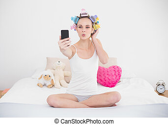 Pouting natural brown haired woman in hair curlers taking a...