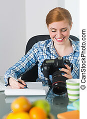 Smiling photographer sitting at her desk looking at camera...