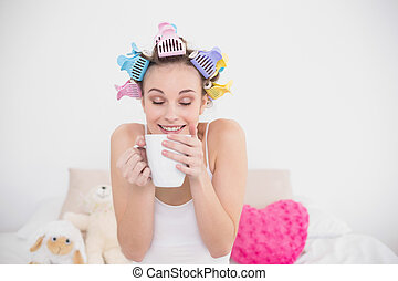 Funny natural brown haired woman in hair curlers enjoying...