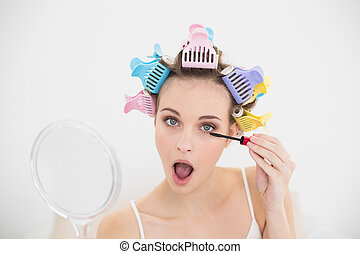 Concentrated natural brown haired woman in hair curlers...