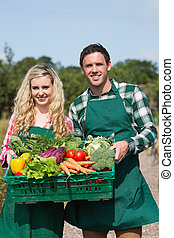 Proud couple showing vegetables in a basket in their garden...