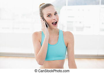 Sporty surprised woman phoning