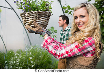 Blonde woman holding a flower basket in a green house...