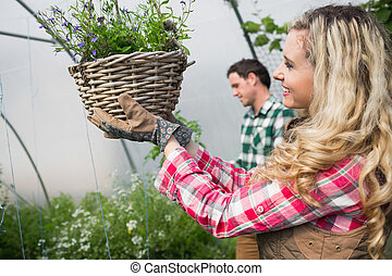 Beautiful woman touching a hanging flower basket in a green...