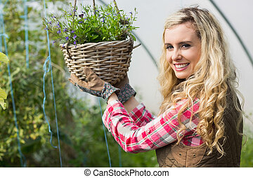 Happy woman touching a hanging flower basket in a green...
