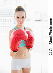 Sporty stern woman boxing in bright room