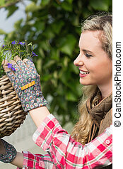 Pretty blonde fixing a hanging flower basket in a green...