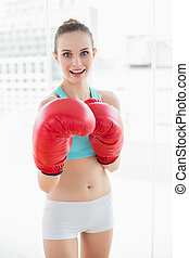 Sporty happy woman boxing in bright room