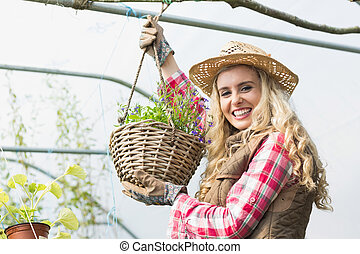 Pretty blonde showing a hanging flower basket in a green...