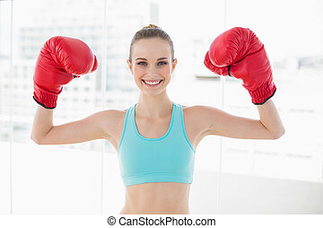 Sporty smiling woman holding up boxing gloves in bright room