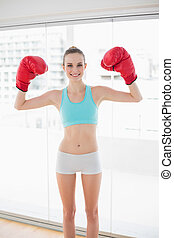 Sporty cheerful woman holding up boxing gloves in bright...