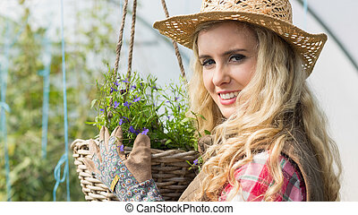 Smiling blonde touching a hanging flower basket in a green...