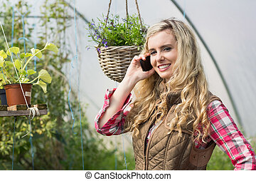 Happy woman mobile phoning in a green house and looking at...