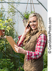 Phoning woman holding a clipboard in her green house smiling...