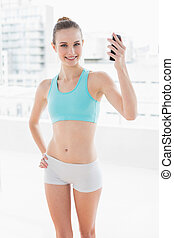Sporty smiling woman holding up smartphone in bright room