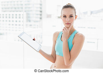 Sporty pensive woman holding a tablet