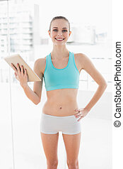 Sporty smiling woman holding a tablet