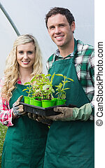 Happy couple showing carton of small plants in a green house