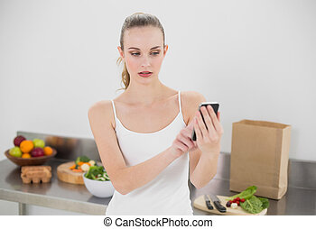 Serious young woman sending a text in the kitchen at home