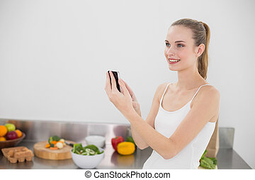 Cheerful young woman sending a texting in the kitchen at...