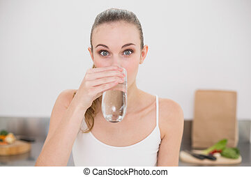 Happy young woman drinking glass of water in the kitchen at...