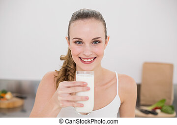Smiling young woman holding glass of milk