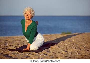 Senior woman doing yoga by the sea