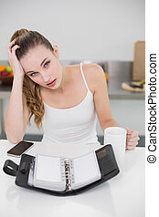 Stressed young woman holding a mug with open diary in the...