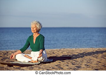 Senior caucasian woman meditating on the beach