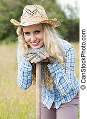 Smiling blonde woman leaning on a shovel wearing gardening gloves looking at the camera