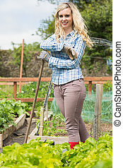 Happy blonde woman standing in her garden looking at the...