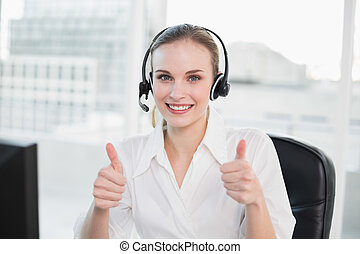 Happy call centre agent looking at camera giving thumbs up...
