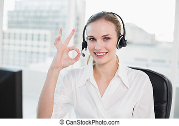 Happy call centre agent looking at camera giving ok sign in...