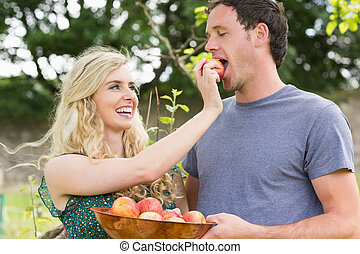 Blonde woman feeding her boyfriend with an apple while...