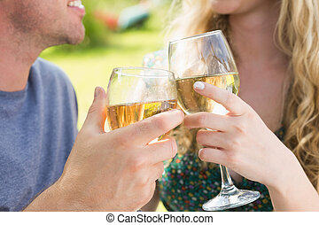Smiling couple toasting with white wine