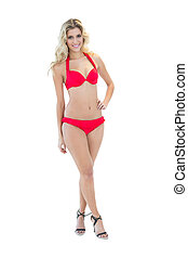 Beautiful smiling blonde model posing with hand on hips...