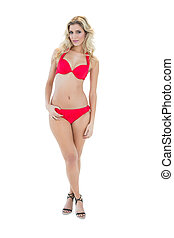 Attractive mysterious blonde model wearing red bikini...