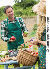 Young handsome farmer selling organic vegetables to pretty...