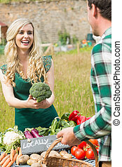 Young female farmer selling organic broccoli to a young man
