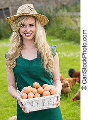Happy young woman holding a basket with eggs