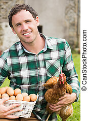 Young man holding his chicken and basket of eggs in his...