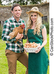 Happy young couple holding chicken and basket of eggs in...